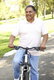 Senior Hispanic Man Riding Bike In Park Stock Images