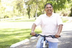 Senior Hispanic Man Riding Bike In Park Royalty Free Stock Photos