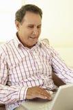 Senior Hispanic Man Using Laptop At Home Royalty Free Stock Images