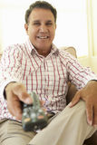 Senior Hispanic Man Using TV Remote Control Stock Image