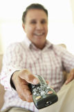 Senior Hispanic Man Using TV Remote Control Stock Photo