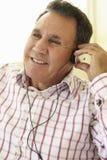 Senior Hispanic Man Wearing Headphones Stock Photography