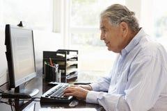 Senior Hispanic man working on computer at home Royalty Free Stock Image