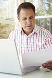 Senior Hispanic Man Working In Home Office Stock Photo