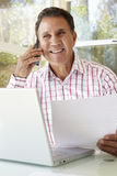 Senior Hispanic Man Working In Home Office Royalty Free Stock Photos