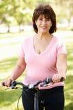 Senior Hispanic woman with bike. In summer park Royalty Free Stock Photo