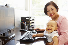 Senior Hispanic woman with computer and baby Royalty Free Stock Photos