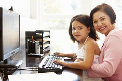 Senior Hispanic woman with computer and grandchild Royalty Free Stock Photography