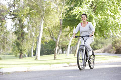 Senior Hispanic Woman Cycling In Park Royalty Free Stock Photography