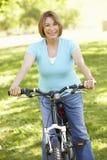 Senior Hispanic Woman Cycling In Park Royalty Free Stock Photo