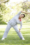 Senior Hispanic Woman Exercising In Park Stock Photo