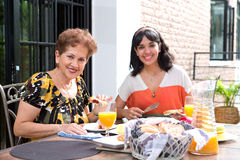 A senior hispanic woman having breakfast outdoors with a daughter Royalty Free Stock Photography
