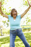 Senior Hispanic Woman With Hula Hoop In Park Stock Images