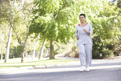 Senior Hispanic Woman Jogging In Park Royalty Free Stock Photo