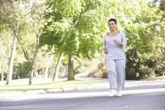 Senior Hispanic Woman Jogging In Park Royalty Free Stock Photo