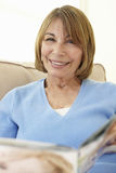 Senior Hispanic Woman Relaxing At Home With Magazine Royalty Free Stock Images