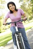 Senior Hispanic Woman Riding Bike In Park Royalty Free Stock Photos