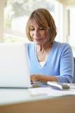 Senior Hispanic Woman Using Laptop In Home Office Royalty Free Stock Photo