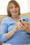 Senior Hispanic Woman Using Smartphone At Home Royalty Free Stock Images