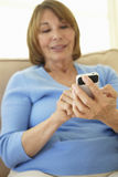 Senior Hispanic Woman Using Smartphone At Home Royalty Free Stock Photography