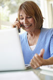 Senior Hispanic Woman Working In Home Office Stock Images