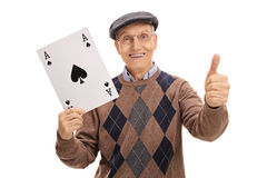 Senior holding ace of spades card and making thumb up sign. Happy senior holding a big ace of spades card and making a thumb up sign isolated on white background Royalty Free Stock Photo