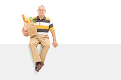 Senior holding bag with groceries seated on panel Royalty Free Stock Photography