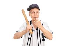 Senior holding baseball bat and blowing a whistle Royalty Free Stock Image