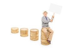 Senior holding blank banner on a pile of coins Royalty Free Stock Photo