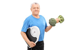 Senior holding broccoli dumbbell and weight scale Royalty Free Stock Photos