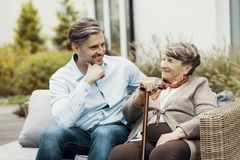 Senior holding a cane while looking at her son stock photo