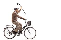 Senior holding a cane and riding a bicycle. Isolated on white background royalty free stock photo