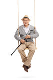 Senior holding a cane and sitting on a swing stock photo