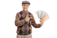 Senior holding a color swatch and pointing. Isolated on white background stock photo