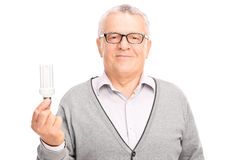 Senior holding an energy efficient light bulb Stock Photo