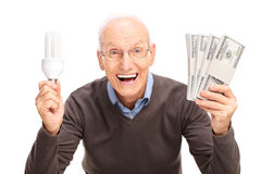Senior holding energy saving light bulb and money Stock Image