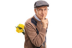 Senior holding flowers and finger on lips Royalty Free Stock Images