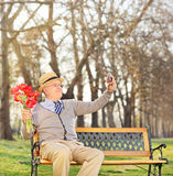 Senior holding flowers and taking selfie in park Royalty Free Stock Photos
