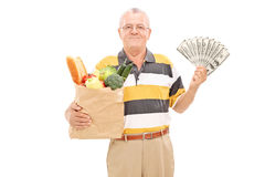 Senior holding a grocery bag and money. Senior holding a grocery bag in one hand and money in the other isolated on white background stock photos