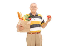 Senior holding grocery bag and a single tomato Royalty Free Stock Photo