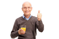 Senior holding a juice and giving a thumb up Royalty Free Stock Images