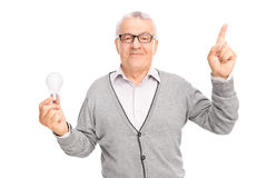 Senior holding a light bulb and pointing with his finger Royalty Free Stock Photo