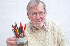 Senior holding a mug of pens and pencils. Stock Photos
