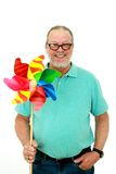 Senior holding a pinwheel Stock Photo