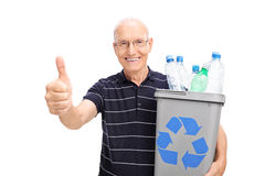 Senior holding a recycle bin full of plastic bottles Royalty Free Stock Images
