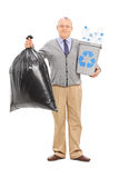 Senior holding a recycle bin and garbage bag Royalty Free Stock Photos