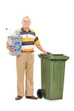 Senior holding recycle bin by a trash can Royalty Free Stock Image