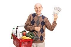 Senior holding a shopping basket and money Stock Photos