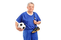 A senior holding a soccer shoes and footbal Royalty Free Stock Photo