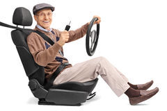 Senior holding steering wheel and car key. Cheerful senior man holding a steering wheel and a car key seated on a vehicle seat isolated on white background Stock Photography